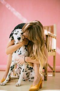 Girl holding her Dalmatian dog.