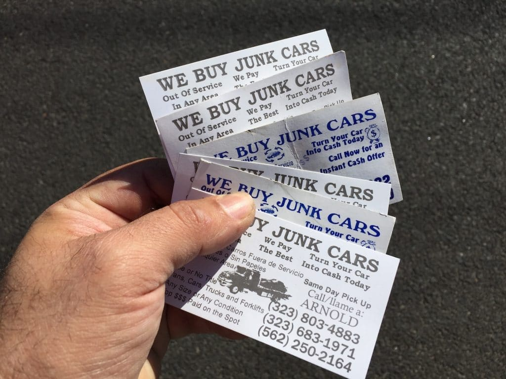 "Close up of hand holding ""we buy your car"" cards. Used to illustrate how irritating they could be when used as an ""outbound marketing"" tactic."
